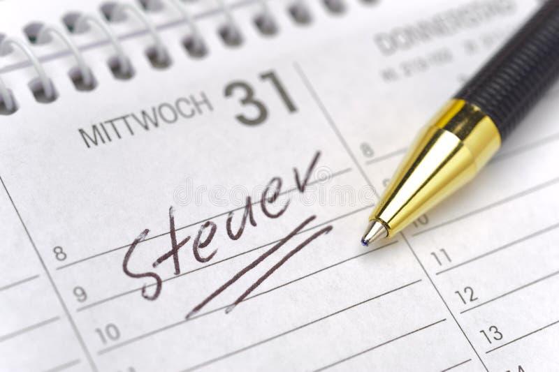 Taxday avlöningsdag i kalender arkivfoto