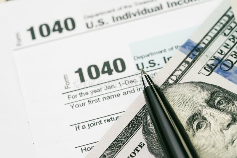 Taxe o conceito do tempo, pena em notas de dólar dos E.U. com o indivíduo de 1040 E.U. imagem de stock