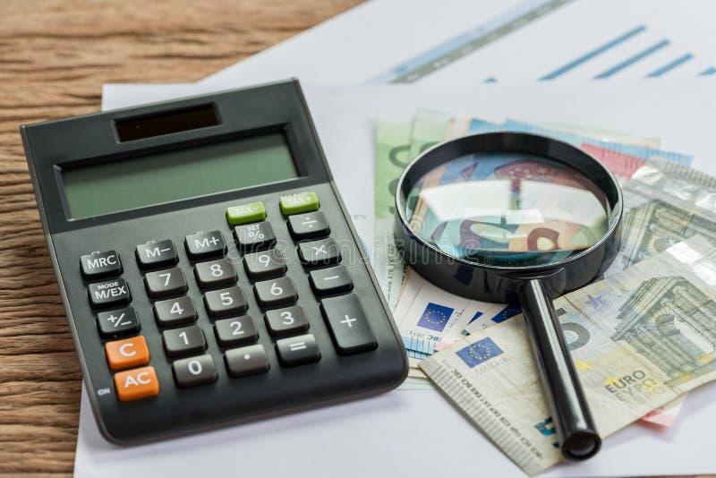 Taxe ou procurando pelo conceito do rendimento, calculadora com gl da lente de aumento fotos de stock royalty free