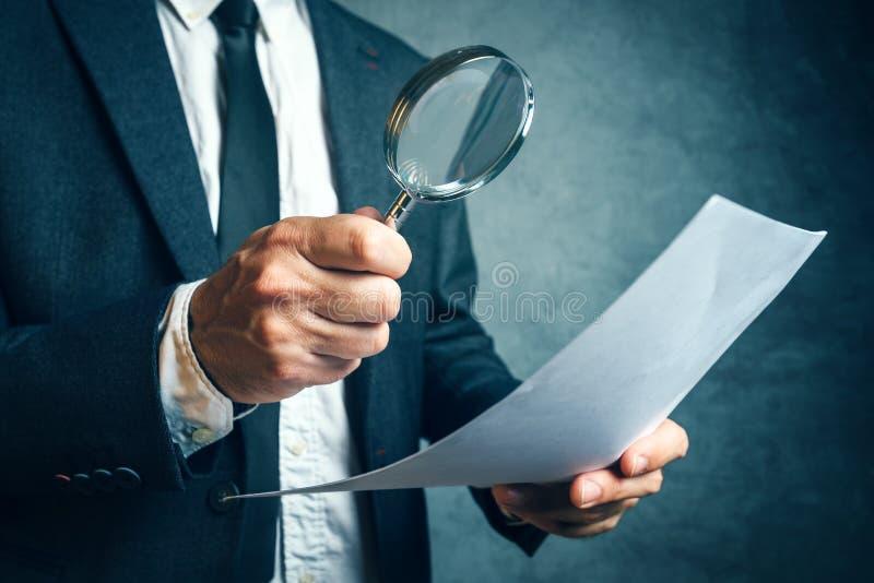 Taxeringsinspektör som utforskar finansiella dokument till och med magnifyi royaltyfri fotografi