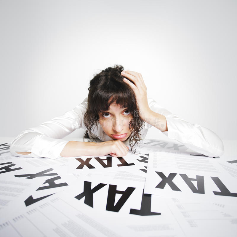 Taxes. Sad woman on her taxes-paperwork covered desk desperately looking at the camera royalty free stock images