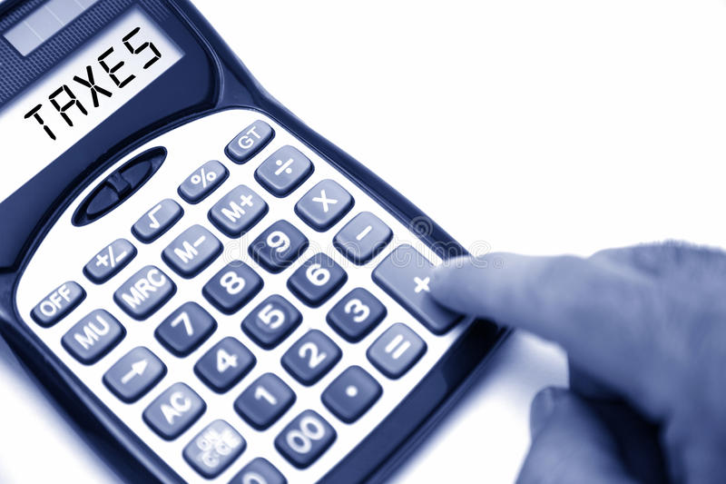 Taxes. Calculator with TAXES text on screen royalty free stock photo