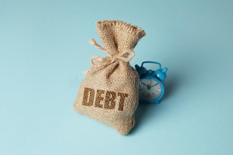 Taxes and interest on debt payments. Overdue payments, penalties. Bag with money and clock on blue background.  stock photography