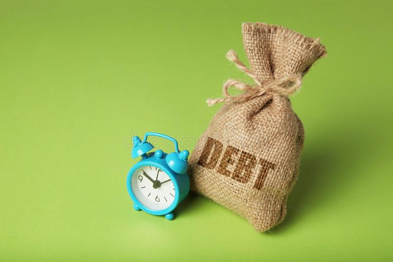 Taxes and interest on debt payments. Overdue payments, penalties. Bag with money and clock on green background.  royalty free stock images