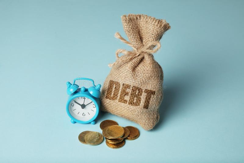 Taxes and interest on debt payments. Overdue payments, penalties. Bag with money and clock on blue background.  stock image