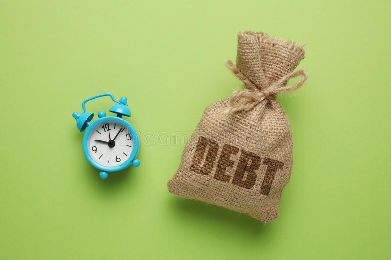 Taxes and interest on debt payments. Overdue payments, penalties. Bag with money and clock on green background.  royalty free stock image