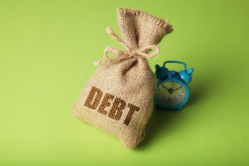 Taxes and interest on debt payments. Overdue payments, penalties. Bag with money and clock on green background.  stock photos
