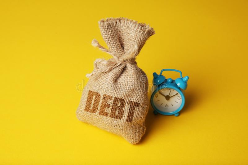 Taxes and interest on debt payments. Overdue payments, penalties. Bag with money and clock on yellow background.  royalty free stock photos