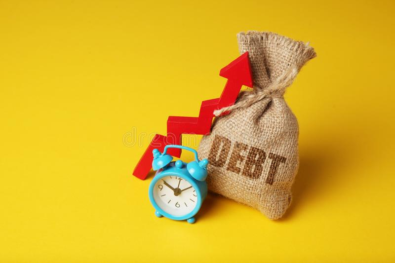 Taxes and interest on debt payments. Overdue payments, penalties. Bag with money and clock on yellow background. Red arrow up.  stock photos