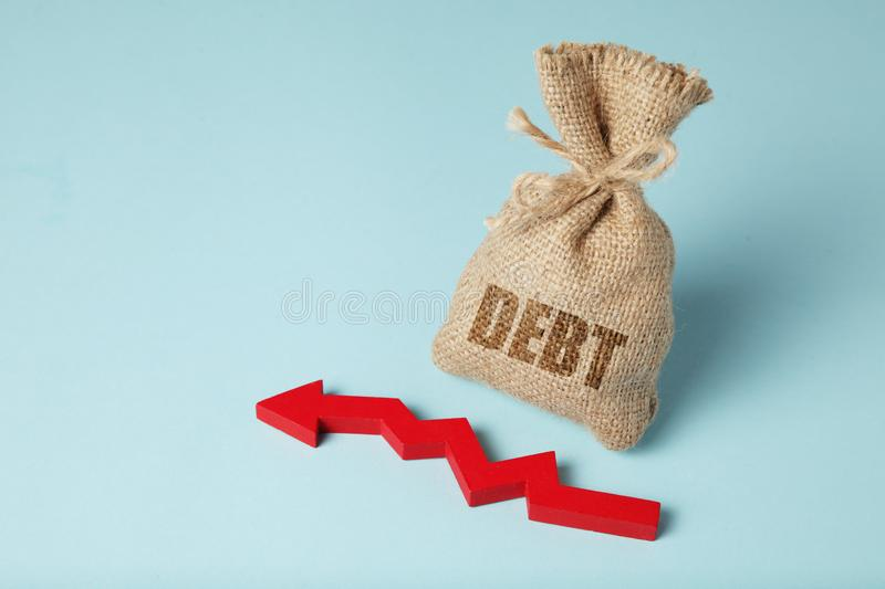 Taxes and interest on debt payments. Overdue payments, penalties. Red arrow and money bag.  royalty free stock image