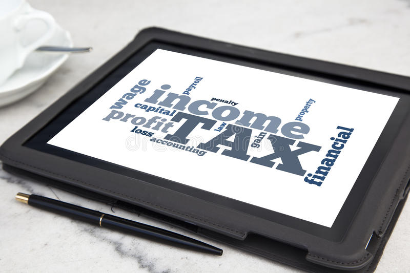 Taxes. Tablet with tax word cloud royalty free stock photo