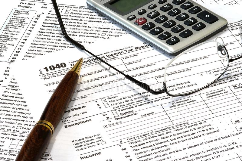 Taxes 1040 Tax Return Form. A 1040 income tax form with a pen, calculator and glasses. The pen obscures the year to add to the image usefulness stock photo