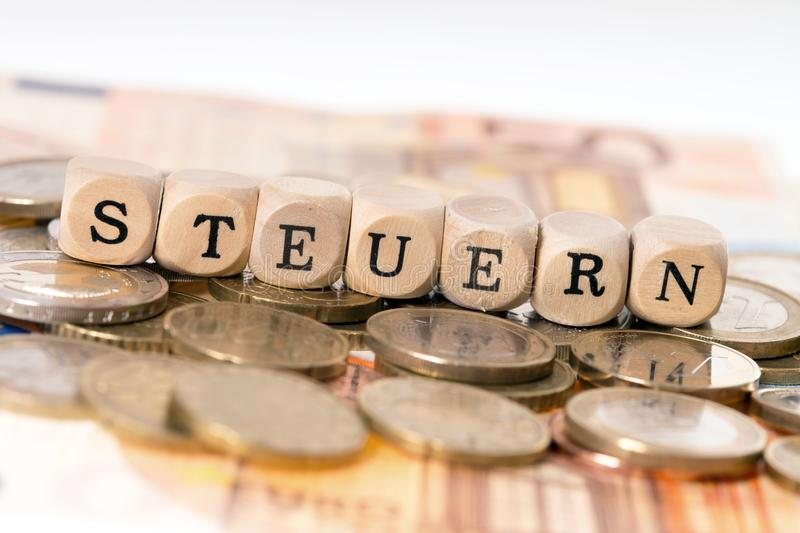 Taxes. Wooden cube with the german word Taxes and euro money stock images