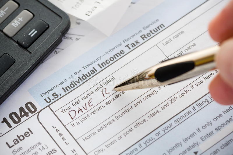 Taxes: Writing Name on 1040 Tax Return. Series for United States Tax season, with 1040 forms, etc royalty free stock images