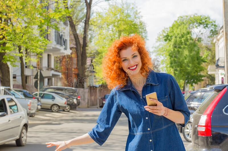 Taxi from app. Pretty happy woman holding mobile phone, hitch hiking in the city street on a sunny day. One single person. Stop stock image