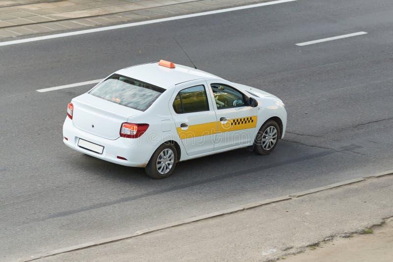 Taxi, biały z żółtym lampasem, tylni widok zdjęcia stock