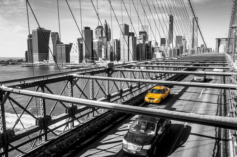 Taxi cab crossing the Brooklyn Bridge in New York. Manhattan skyline in background stock images