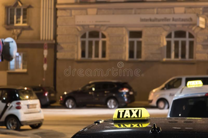 Taxi cab sign on top of the vehicle at nighttime stock images