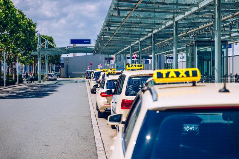 Taxi cabs waiting for passengers. Yellow taxi sign on cab cars. Taxi cars waiting arrival passengers in front of Airport Gate. royalty free stock photography