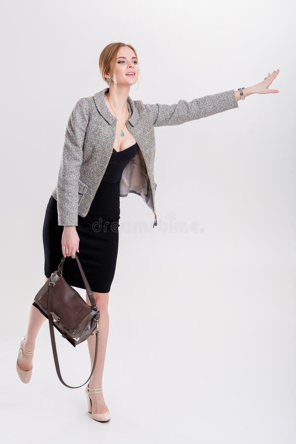 Taxi contagieux de femme jeune femme d'affaires dans l'ondulation noire de robe photo libre de droits