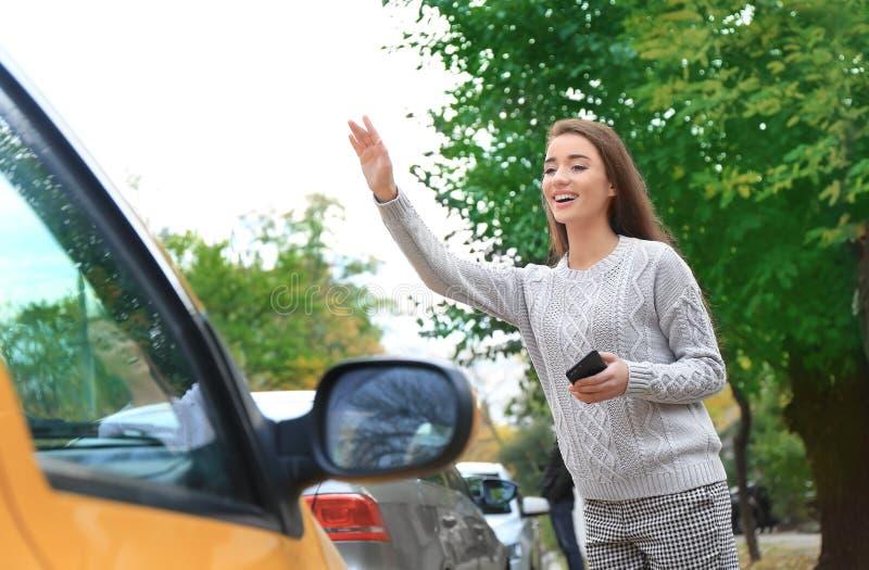 Taxi de cogida de la mujer joven imágenes de archivo libres de regalías