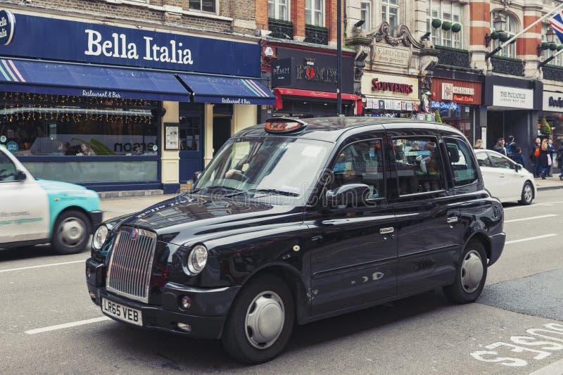 Taxi de Londres conduit sur l'avenue de Shaftesbury, une rue importante à la fin le West End de Londres près de cirque de Piccadi photographie stock libre de droits