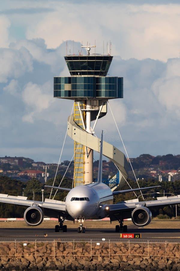 Taxi de los aviones de Singapore Airlines Boeing 777 después de aterrizar en Sydney Airport con la torre de controlador aéreo imagenes de archivo