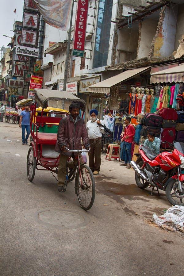 Taxi de vélo de pousse-pousse à la recherche des clients au bazar principal Paharganj en capitale indienne photographie stock