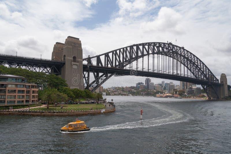 Taxi dell'acqua che entra in Quay circolare con Sydney Harbour Bridge sui precedenti immagini stock libere da diritti