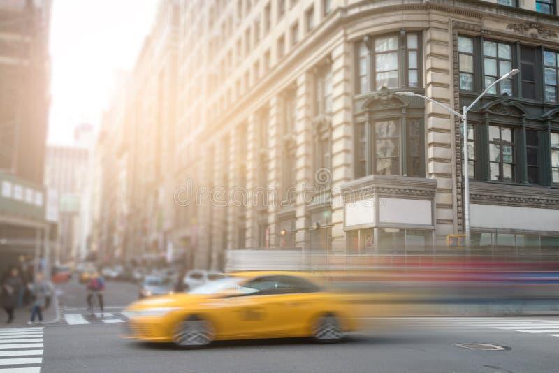 Taxi di giallo di New York che accelera attraverso Manhattan immagine stock libera da diritti