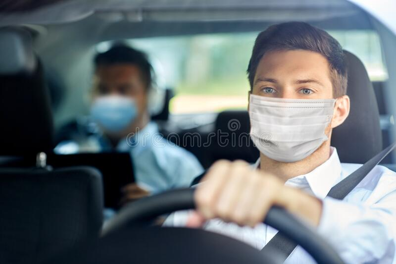 Taxi driver in face protective mask driving car. Health protection, safety and pandemic concept - male taxi driver wearing face protective medical mask driving stock photography