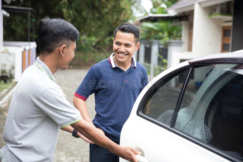 Taxi driver opening the car door. Asian male taxi driver opening the car door for his customer stock images