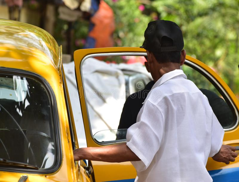 Taxi driver is opening the door of a car stock photograph stock photos