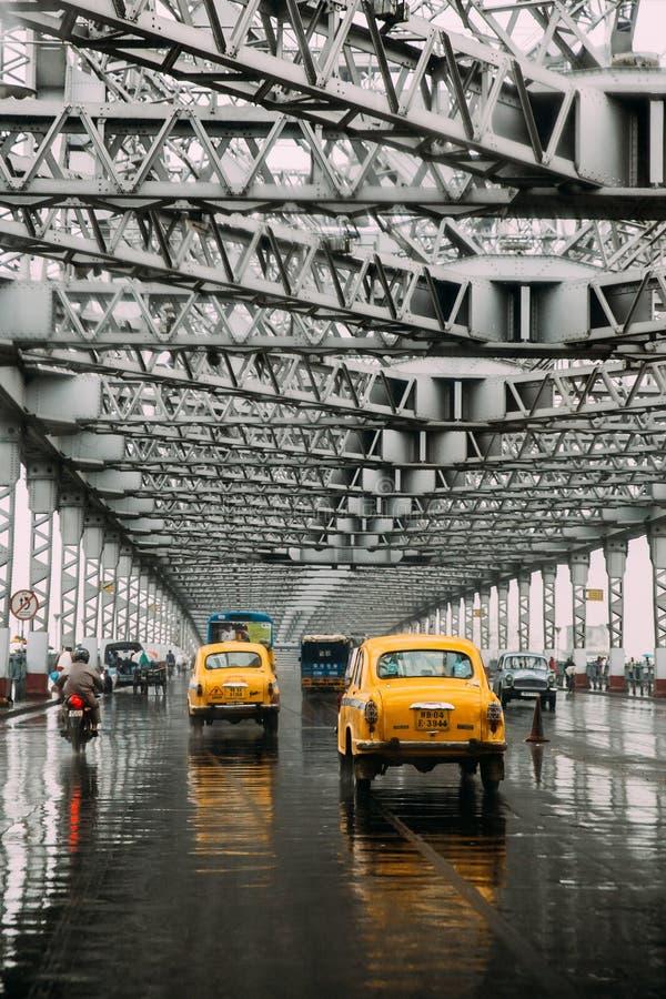 Taxi gialli che corrono sulla strada dentro il ponte di Howrah nel pomeriggio con pioggia in Calcutta, India fotografia stock libera da diritti