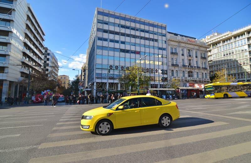 Taxi giallo e la gente che aspettano per attraversare la strada al sintagma Atene Grecia immagini stock libere da diritti