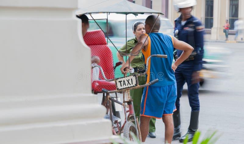 Taxi jeździec opowiada stoi bezczynnie jego taxi podczas gdy umundurowana policja obserwuje ruchliwą ulicę zamazującą w tle obraz royalty free
