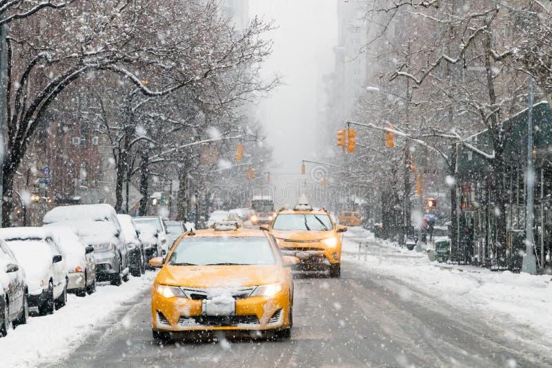 Taxi kör ner en snö täckt 5th aveny under en vinterstorm i New York City royaltyfri foto
