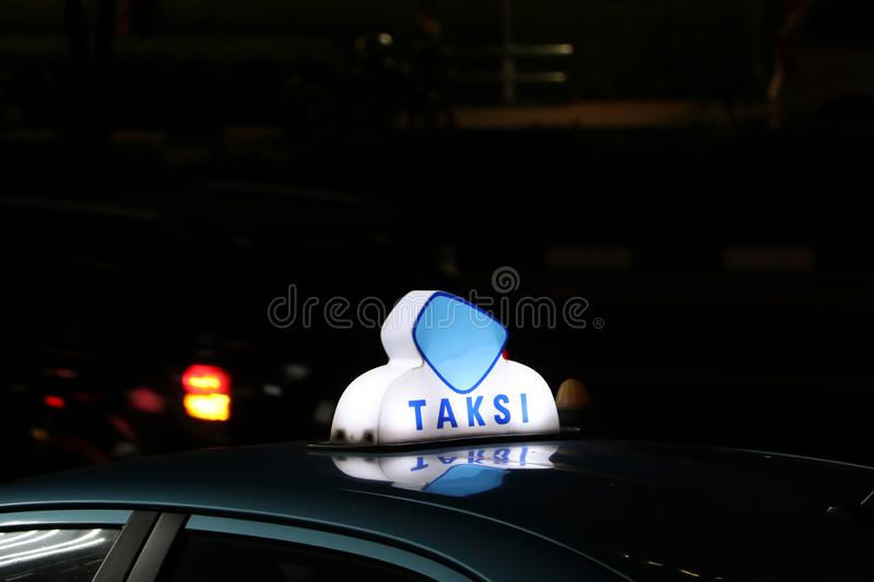 Taxi light sign or cab sign in blue and white color on the car roof at the street in the dark night royalty free stock photography