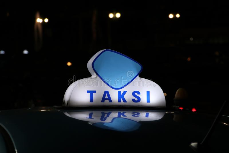 Taxi light sign or cab sign in blue and white color on the car roof at the street in the dark night. With text TAKSI in Indonesia royalty free stock photography