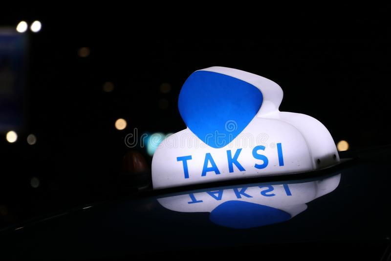 Taxi light sign or cab sign in blue and white color on the car roof at the street in the dark night. With text TAKSI in Indonesia stock images