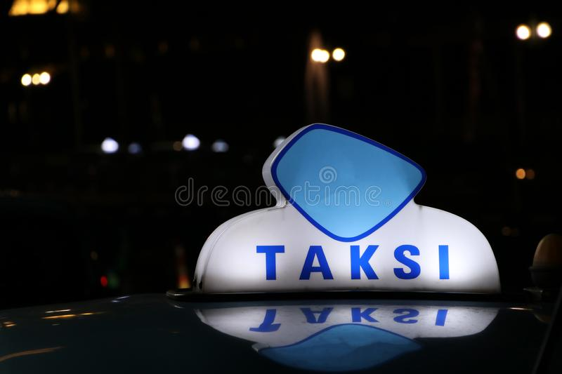 Taxi light sign or cab sign in blue and white color on the car roof at the street in the dark night stock image