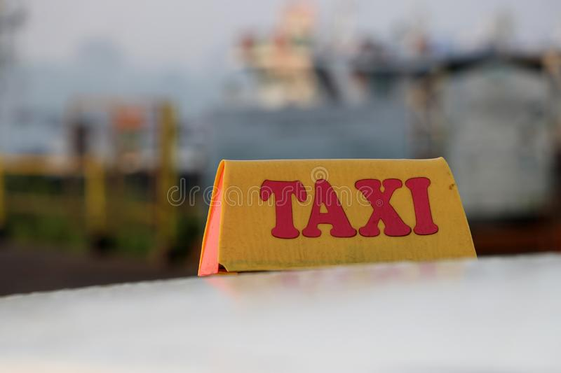 Taxi light sign or cab sign in drab yellow color with red text on the car roof royalty free stock photos