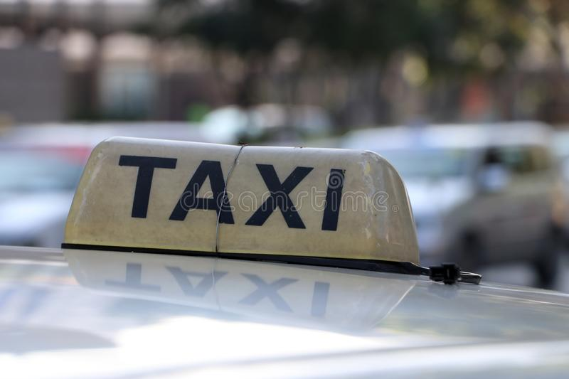 Taxi light sign or cab sign in brown color with black text and tied with wire on the car roof at the street royalty free stock photography