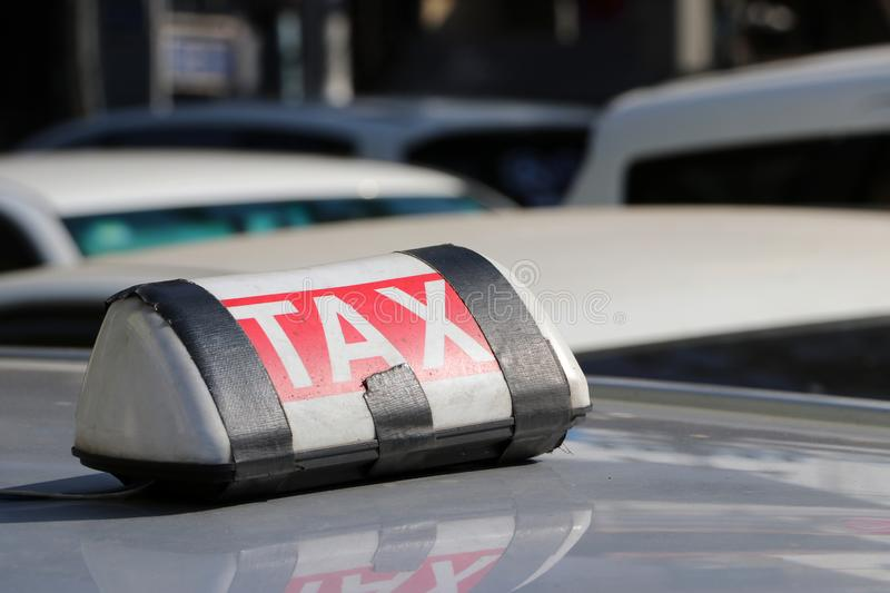 Taxi light sign or cab sign in white and red color with white text and tied with black tape on the car roof at the street stock photos
