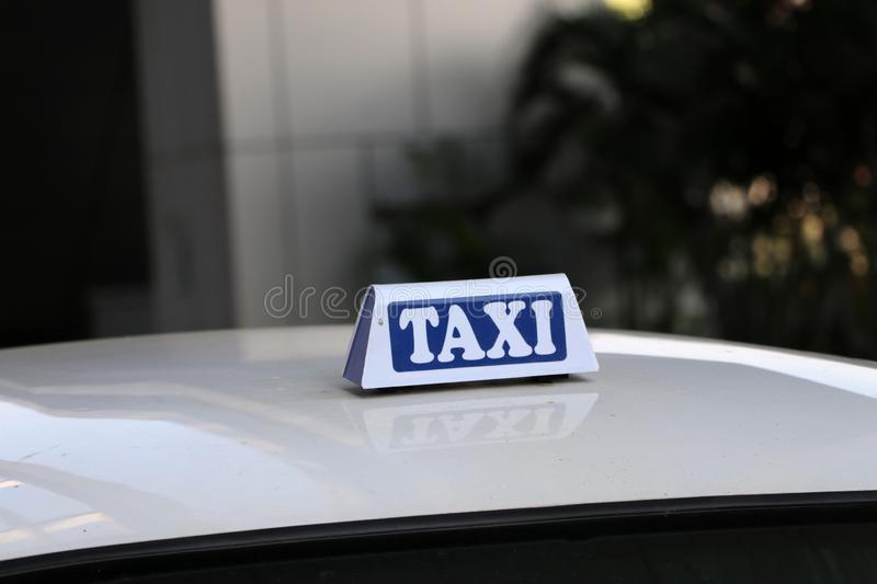 Taxi light sign or cab sign in white and blue color with white text on the car roof at the street blurred background stock photos