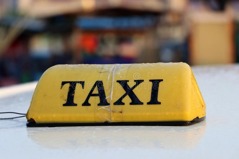 Taxi light sign or cab sign in yellow color with black text and tied with transparent tape on the car roof stock photo