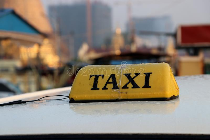 Taxi light sign or cab sign in yellow color with black text and tied with transparent tape on the car roof at the street blurred stock photo