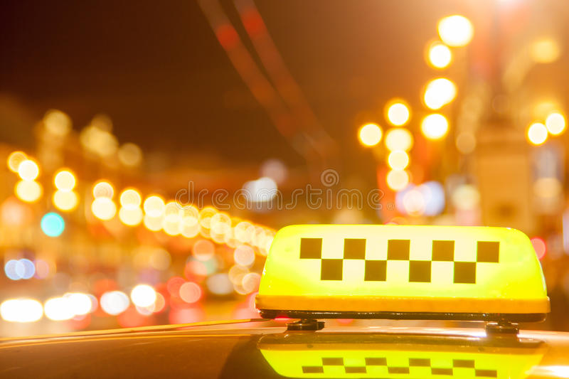 Taxi o tampão em um telhado do carro contra a cidade imagem de stock