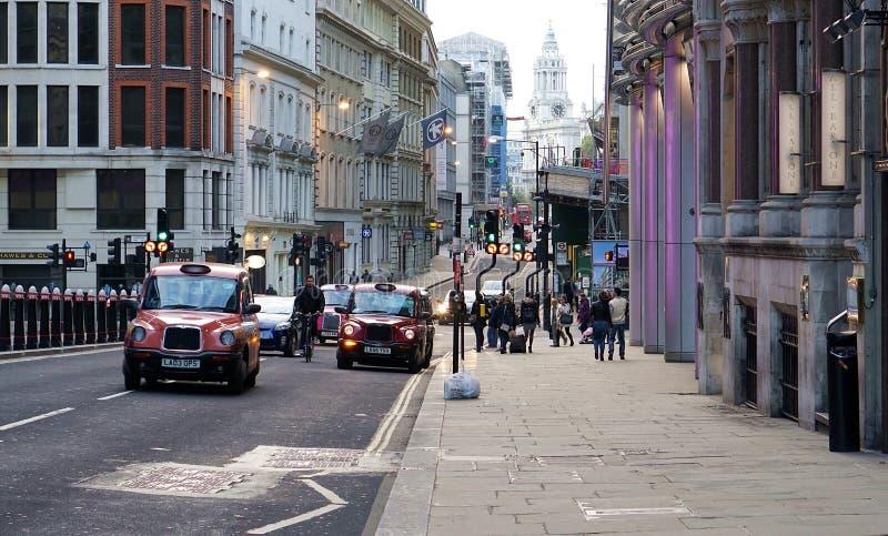 Taxi och cyklist på en London gata royaltyfri foto