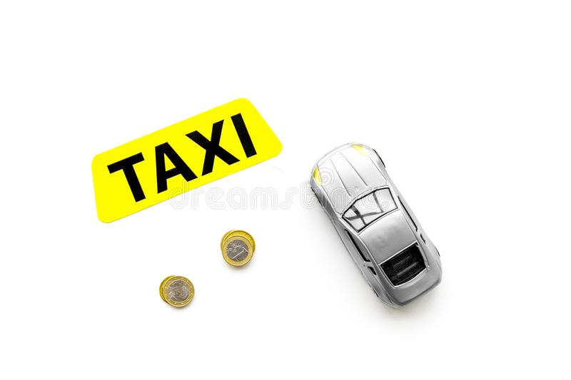 Taxi operator concept. Chip service. Price of services. Sign taxi ner car toy and coins on white background top view stock image